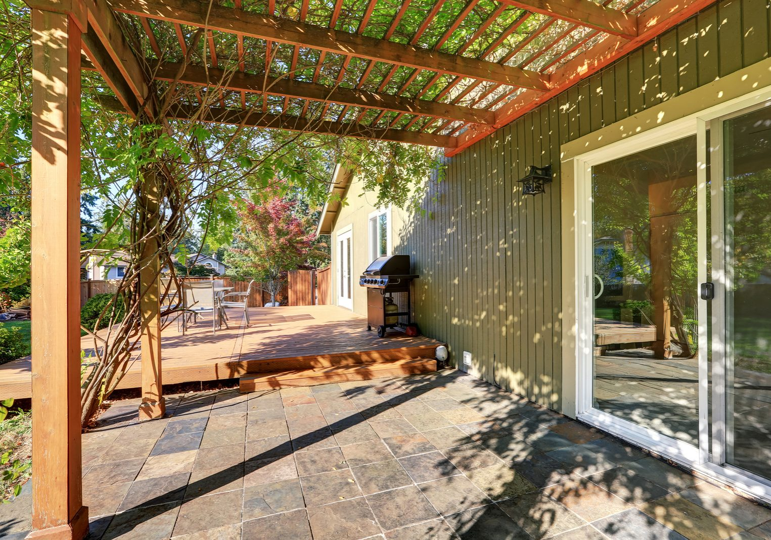 Back yard with pergola tile floor and wooden walkout deck Northwest USA