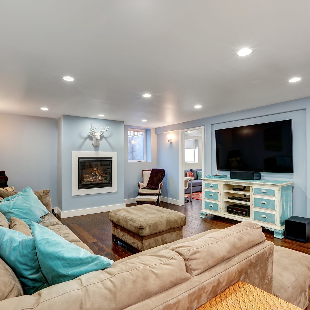 Pastel blue walls in basement living room interior. Large corner sofa with blue pillows and ottoman. Vintage white and blue TV cabinet. Northwest USA