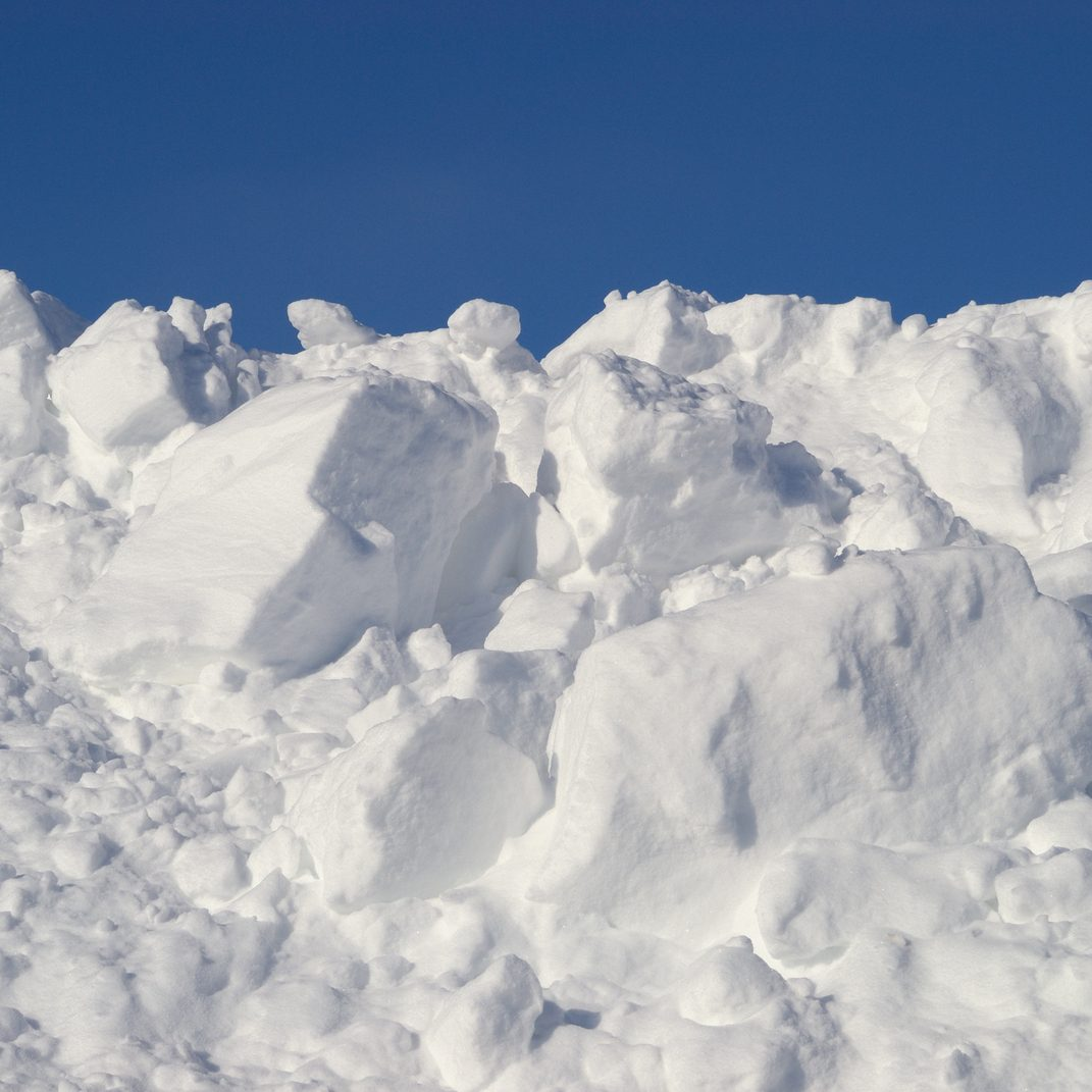 Large pile of plowed snow against blue sky