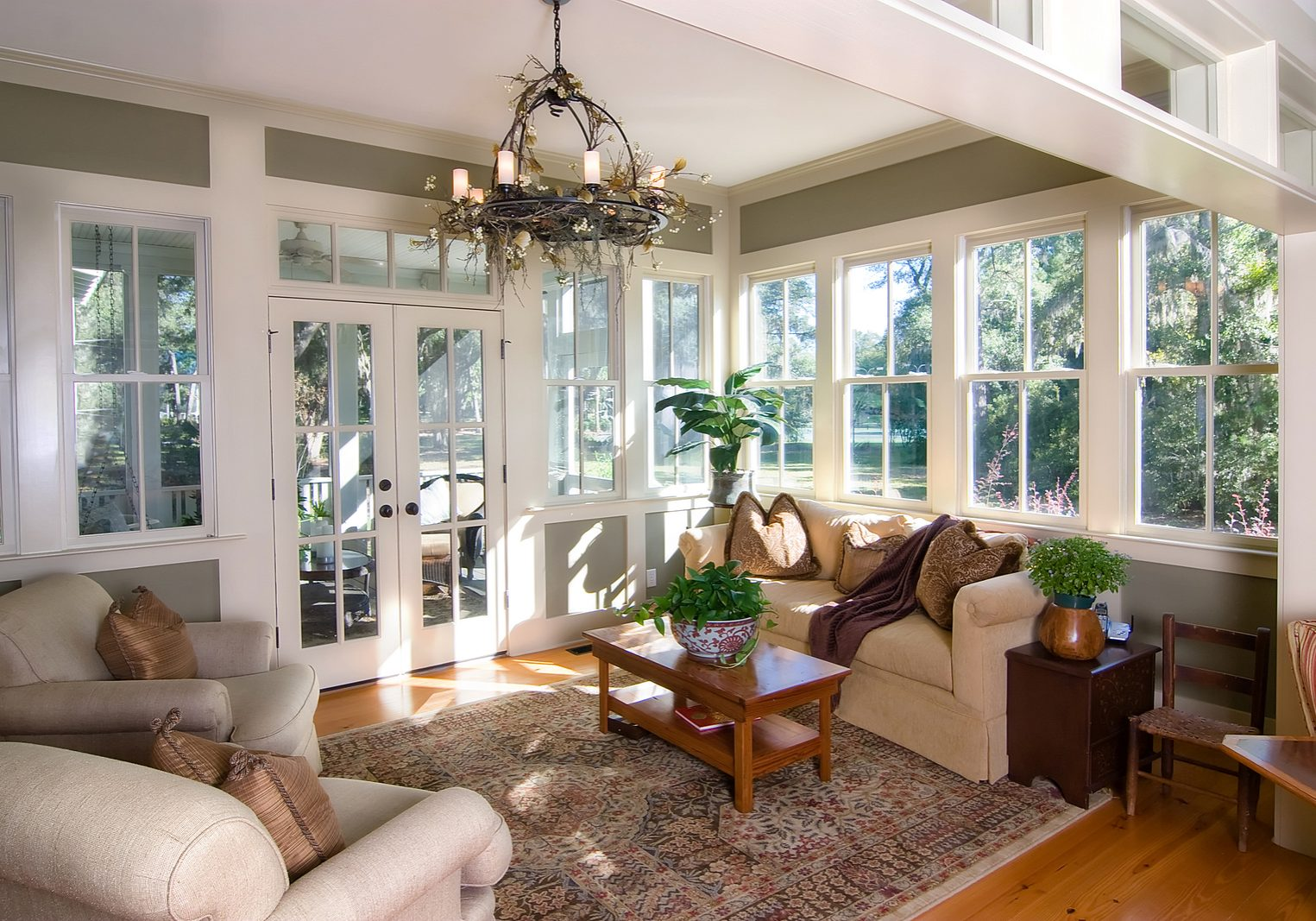 furnished sunroom with large windows and glass doors