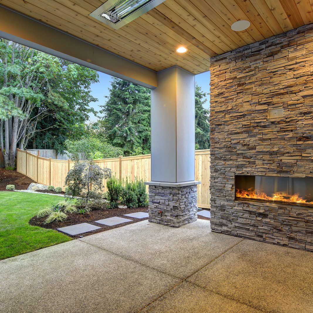 Outside Patio features natural wood plank ceiling concrete floor and oversized stone fireplace overlooking a beautiful expansive yard. Northwest USA